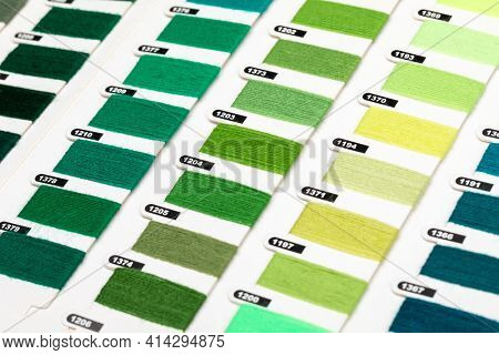 Green and yellow color hue yarn thread sample swatches close-up