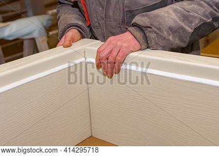 Carpentry Worker Puts Together Wooden Pieces Of Door Frame In Carpentry Workshop.