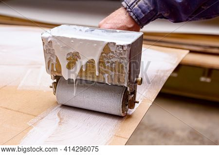 Close Up Shot On Carpentry Worker Who Uses Handy Roller Tool, Spreader For Applying Adhesive On The