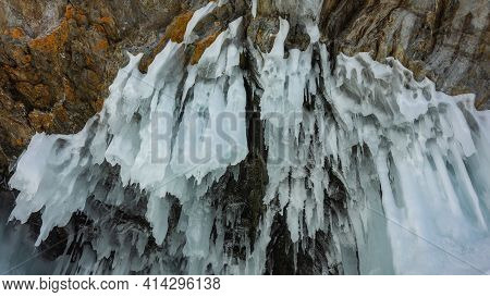 Amazing Bizarre Icicles Hang From The Roof Of The Grotto In The Rock. Stone And Ice Texture.