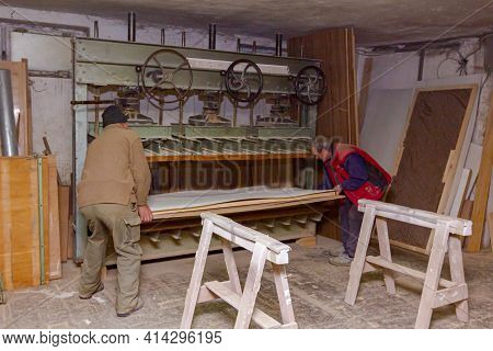 Carpenter Workers Are Putting Wooden Profiles Smeared With Glue In The Wood Press Machine For Squeez