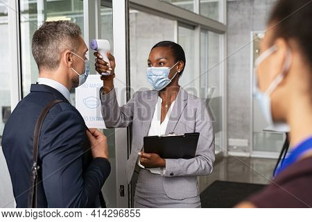 African businesswoman using gun thermometer to check body temperature of people during Covid pandemic. Receptionist checking forehead temperature of businessman before entering in office building.