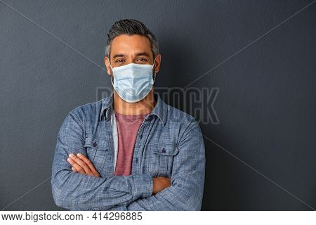 Mature man wearing protective face mask isolated against grey wall. Smiling indian man wearing surgical mask while looking at camera. Portrait of mixed race guy standing isolated on gray background.