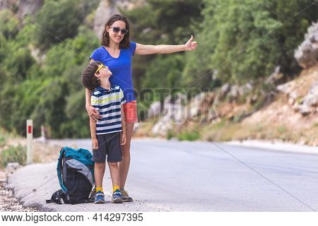 A Woman With A Child Stop The Car On The Road, A Hitchhiker With Children, A Boy With A Mother Hitch