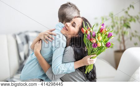 Young Mother Receiving A Bouquet Full Of Tulips From His Son During National Mothers Day And His Son