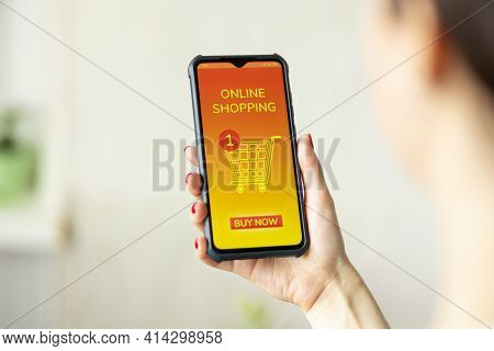 A Woman Holds A Cellphone In Her Hand. An App With Shopping Cart Is Opened On The Device Screen. Blu