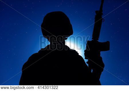 Night Silhouette Of Army Special Operations Forces Soldier Standing With Service Rifle On Background
