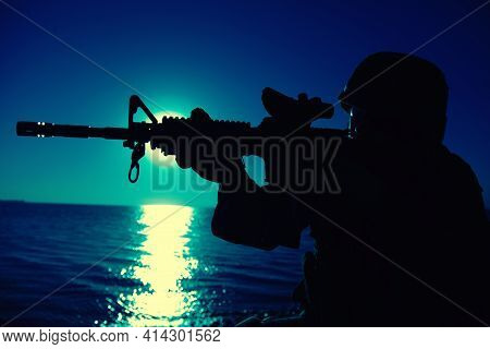 Modern Army Infantry Soldier, Coast Guard Rifleman Aiming Assault Rifle With Collimator Sight At Nig