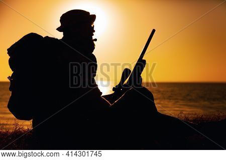 Silhouette Of Commando Fighter, Army Special Forces Sniper Sitting On Sea Or Ocean Shore On Sunset.