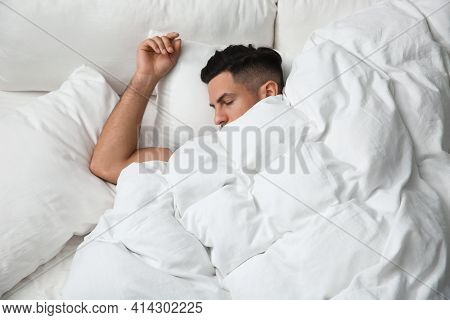 Handsome Man Sleeping Under Soft Blanket In Bed At Home, Above View