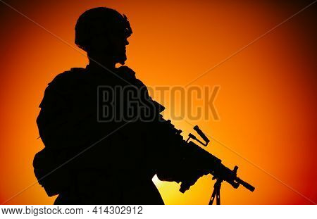 Silhouette Of Army Infantry Soldier, Commando In Combat Helmet, Armed Light Machine Gun, Standing On