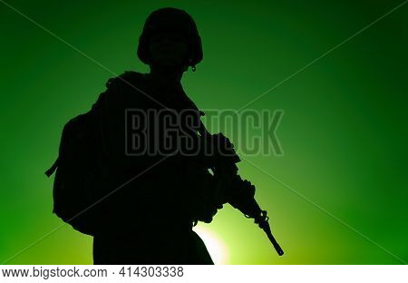 Silhouette Of Army Rifleman In Helmet And Ammunition, Carrying Tactical Backpack, Walking With Servi