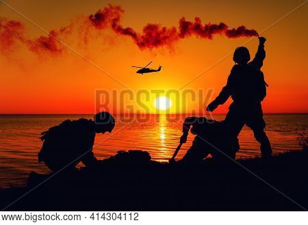 Silhouette Of Army Special Forces Infantry Soldiers, Marines Or Navy Seals Team Signaling To Helicop