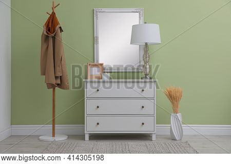 White Chest Of Drawers With Decor, Coat Stand And Mirror In Hallway. Interior Design