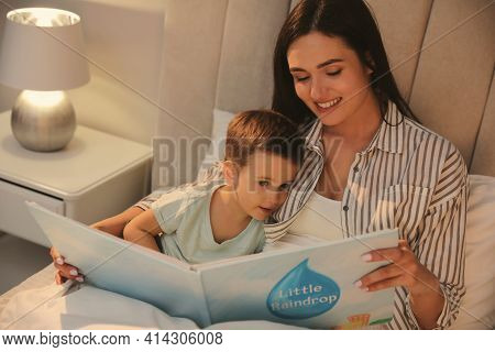 Mother Reading Bedtime Story To Her Son At Home