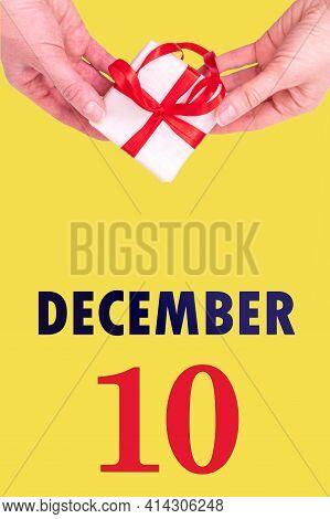 December 10th. Festive Vertical Calendar With Hands Holding White Gift Box With Red Ribbon And Calen