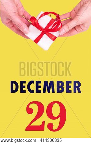 December 29th. Festive Vertical Calendar With Hands Holding White Gift Box With Red Ribbon And Calen