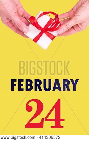 February 24th. Festive Vertical Calendar With Hands Holding White Gift Box With Red Ribbon And Calen
