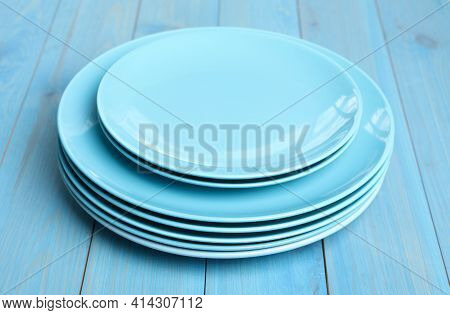 Empty Clean Ceramic Dishware On Turquoise Wooden Table, Closeup
