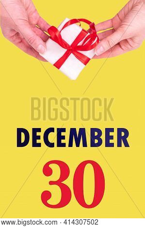 December 30th. Festive Vertical Calendar With Hands Holding White Gift Box With Red Ribbon And Calen