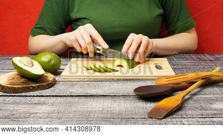 The Girl Cuts A Ripe Green Avocado With A Knife. Cooking. The Fruits Are Cut On A Wooden Cutting Boa