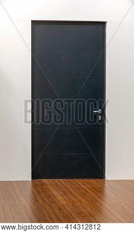 Closed Black Door In Room With Laminate Floor