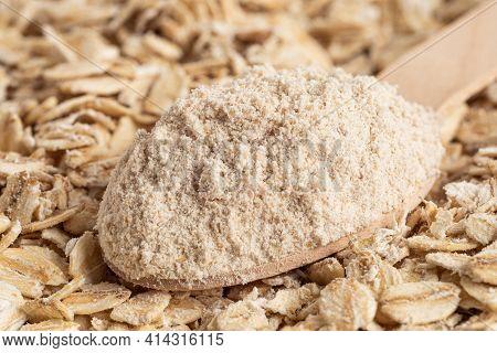 Spoonful Of Oat Flour On Top Of Uncooked Porridge Oats. Blur. Background.