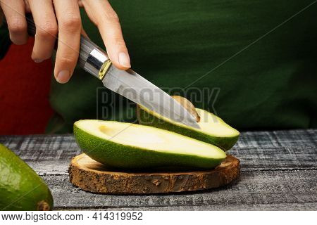 Cut The Avocado With A Knife. Fresh Avocado On A Round Cutting Board. Girl Cuts An Avocado With A Kn
