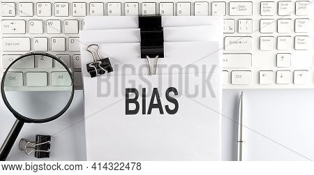 Words Bias Written On Papers On Computer Keyboard With Magnifier And Pen