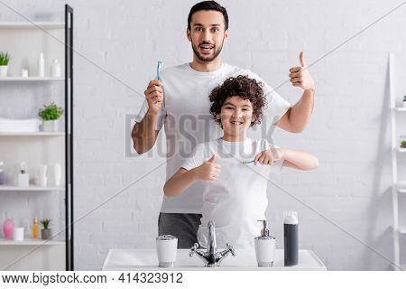 Arabian Son And Father Showing Like While Holding Toothbrushes In Bathroom.