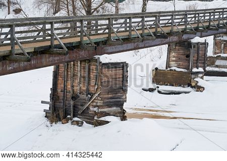Abstract Empty Old Wooden Bridge Closeup On The River And With Snow In Winter Or Spring In A Vintage
