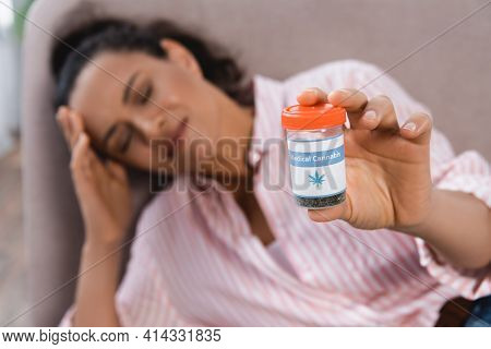 Blurred African American Woman Suffering From Migraine And Holding Bottle With Medical Cannabis In L