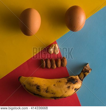 Egg Banana And Some Nuts Make Smiley Face On Colorful Background,nose And Teeth Made With Nuts