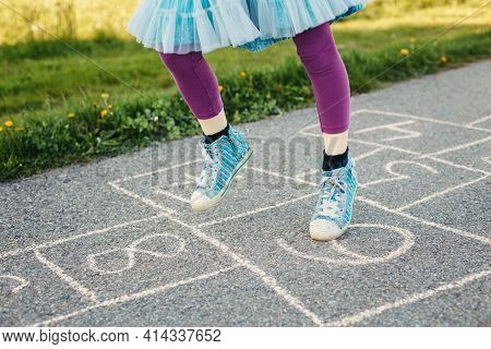 Closeup Of Chld Girl Playing Jumping Hopscotch Outdoor. Funny Activity Game For Kids On Playground O