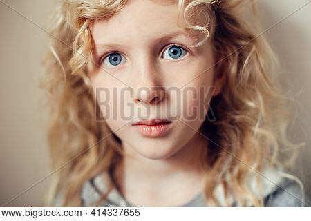 Closeup Portrait Of Beautiful Pensive Serious Caucasian Blonde Girl With Long Hair On Light Neutral