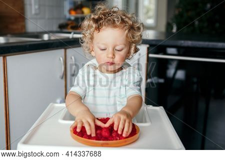 Healthy Eating. Cute Caucasian Baby Boy Eating Ripe Red Fruits At Home. Funny Child Kid Sitting High