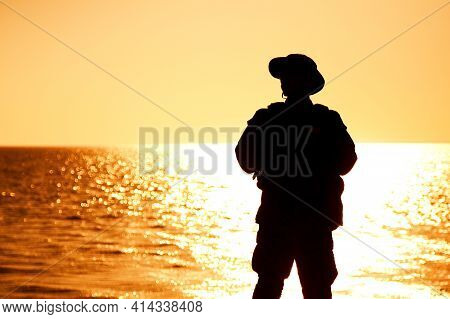 Silhouette Of Army Infantry Soldier, Coast Guard Fighter In Boonie Hat, Standing On Shore, Sunset An