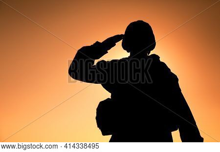 Silhouette Of Soldier In Combat Helmet And Ammunition Saluting On Background Of Sunset Sky. Army Spe