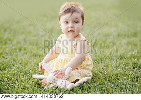 Funny Baby Kid With Toy. Cute Adorable Baby Girl In Yellow Dress Sitting On Grass In Park Outdoor. F