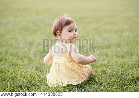 Funny Baby Kid. Cute Adorable Baby Girl In Yellow Dress Sitting On Grass In Park Outdoor And Looking