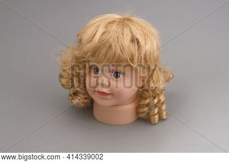 The Head Of A Mannequin Of A Little Girl With Golden Curls On A Gray Background.shop Concept, Sale,