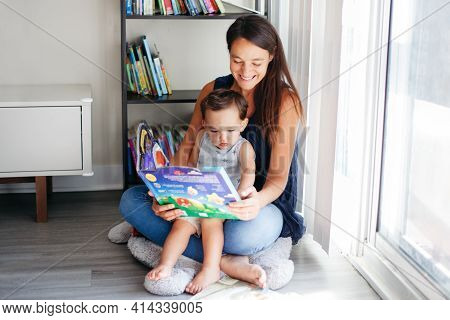 Mother With Son Boy Sitting On Floor At Home And Reading Book Together. Child Kid Early Development