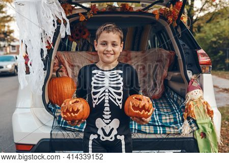 Trick Or Trunk. Boy Child With Red Carved Pumpkins Celebrating Halloween In Trunk Of Car. Happy Kid