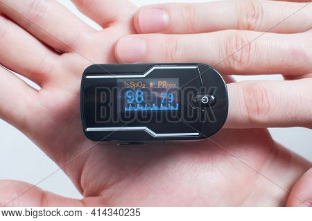 Pulse Oximeter On The Index Finger Against The Background Of The Palm. Measurement Of Blood Oxygen A
