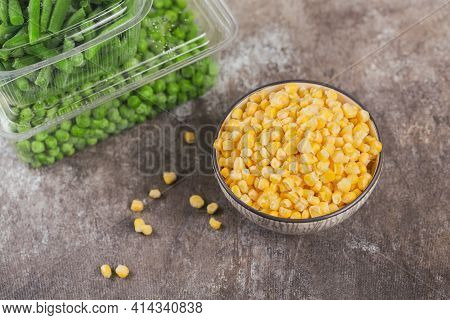 Plastic Container With Different Organic Deep Frozen Vegetables On Table. Green Peas, Sweet Corn And