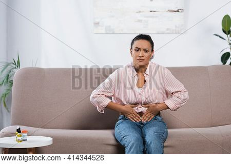 African American Woman Suffering From Abdominal Pain While Sitting On Couch In Living Room.