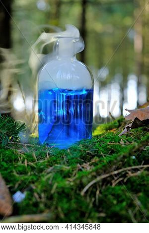 Herbal Blue Potion.herbal Elixir On A Mossy Stump On A Forest Background.magic Potion. Homeopathic M