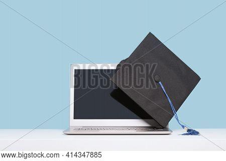 Black Graduation Cap With Blue Ribbon On Laptop
