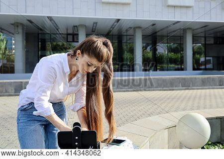 Young Beautiful Woman With Long Hair Wants To Get Something From Handbag To Fix Her Hairstyle. On De