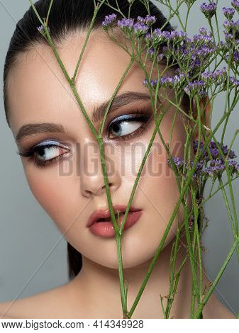 Portrait Of Young Beautiful Woman Standing Behind A Branch Of Violet Flowers